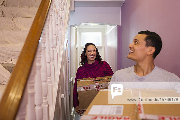 Happy couple moving into new house  carrying cardboard boxes in corridor