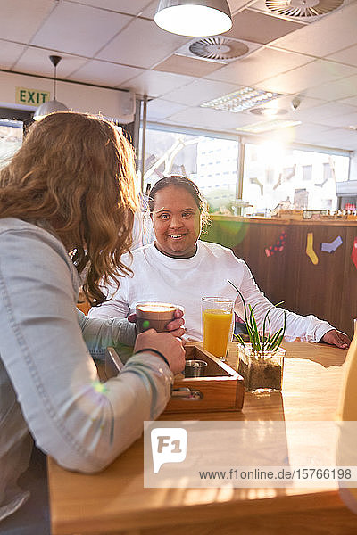 Young woman with Down Syndrome talking with friend in cafe