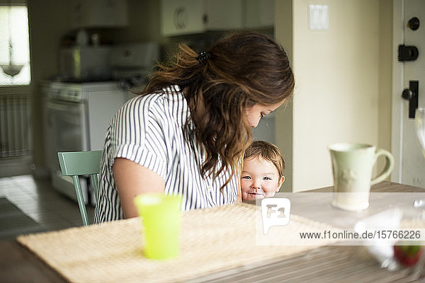 Mother and cute toddler daughter at kitchen table
