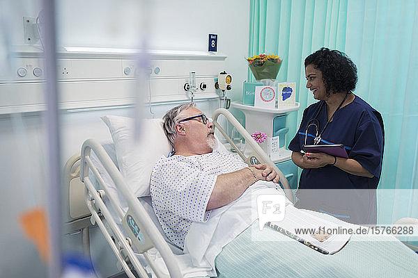 Arzt mit digitalem Tablet bei der Visite  Gespräch mit älterem Ehepaar im Krankenhauszimmer