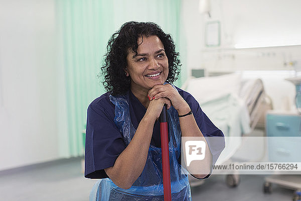 Lächelnde Krankenpflegerin bei der Reinigung einer Krankenstation