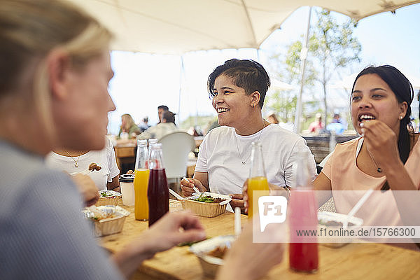 Smiling women friends enjoying lunch at farmer's market