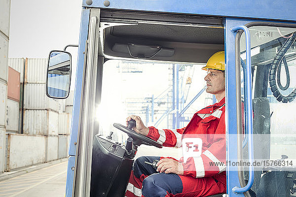 Dock worker operating cargo container forklift at shipyard