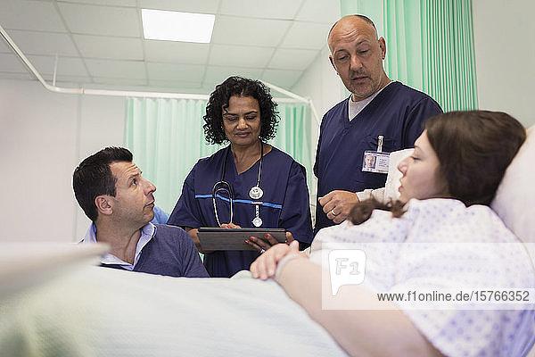 Ärzte bei der Visite  Gespräch mit Paar im Krankenhauszimmer