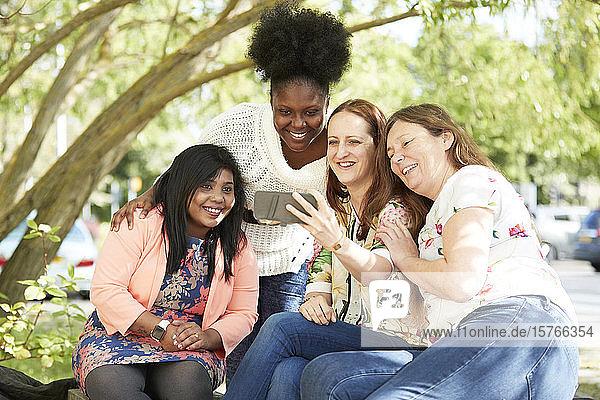 Happy female friends using smart phone in park