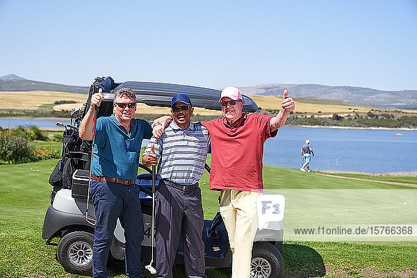 Portrait happy mature male golfers at golf cart on sunny course