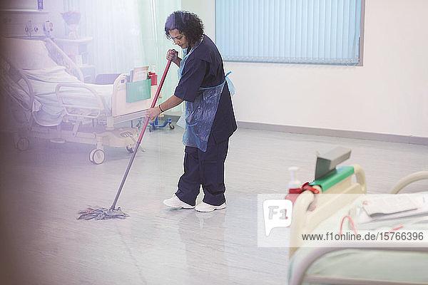 Weiblicher Krankenpfleger wischt den Boden einer Krankenhausstation