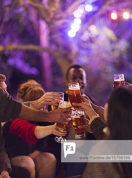 Friends toasting beer glasses at party