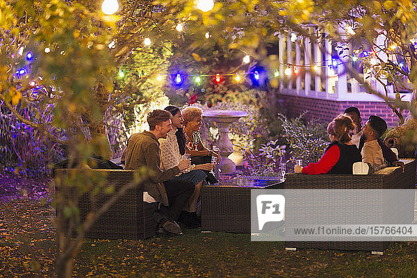 Friends talking and drinking under trees with string lights at garden party Friends talking and drinking under trees with string lights at garden party