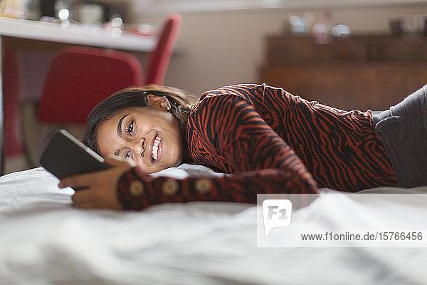 Smiling teenage girl using smart phone on bed