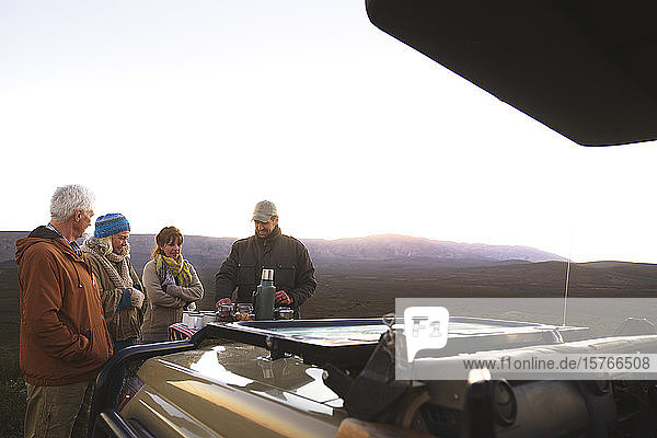Safari tour guide and group enjoying coffee outside off-road vehicle