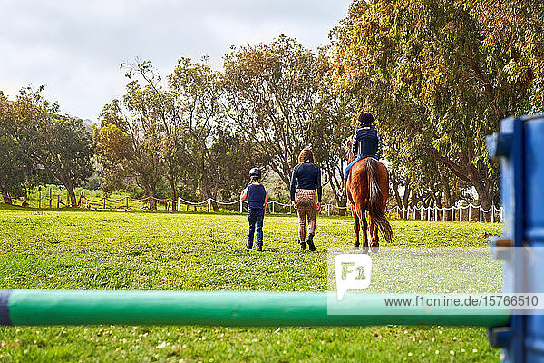 Woman teaching girls horseback riding in sunny rural grass paddock
