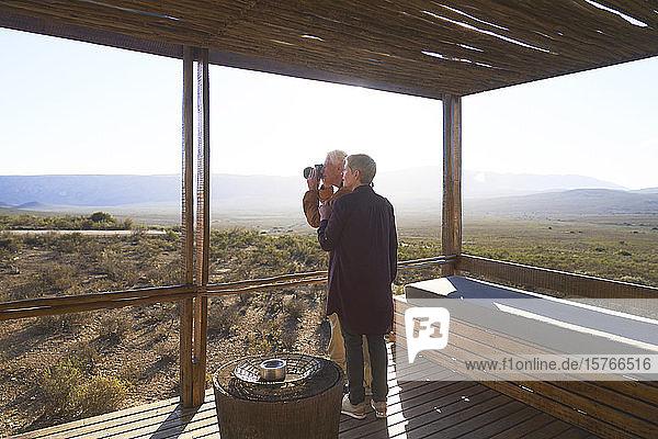 Älteres Paar mit Kamera auf dem sonnigen Balkon einer Safarikabine