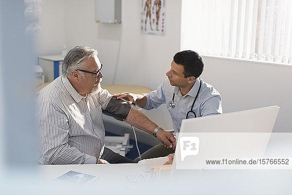 Männlicher Arzt prüft den Blutdruck eines älteren Patienten in einer Arztpraxis