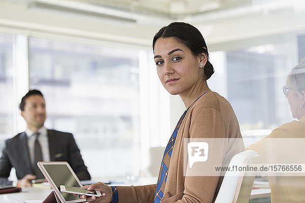 Portrait confident businesswoman with smart phone in conference room meeting