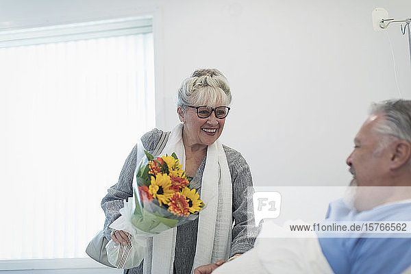 Happy senior woman bringing flower bouquet to husband recovering in hospital room Happy senior woman bringing flower bouquet to husband recovering in hospital room