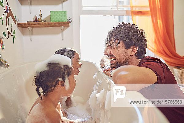 Verspielter Vater gibt Kleinkind Töchter Schaumbad
