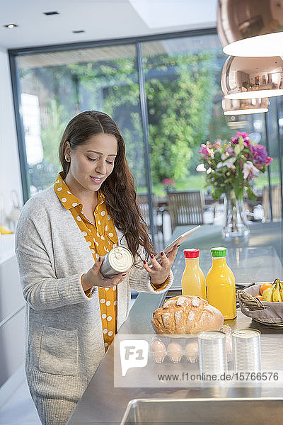 Woman with digital tablet checking food labels in kitchen