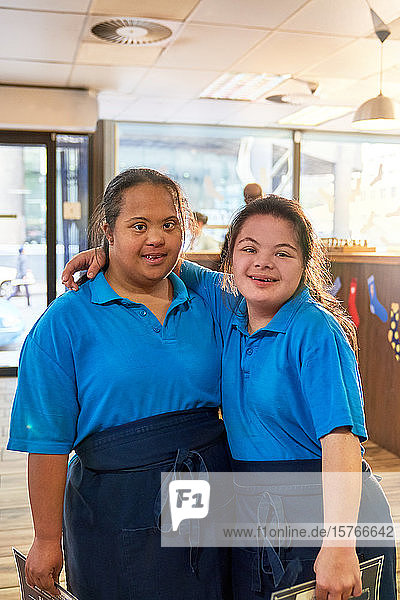 Portrait confident young women with Down Syndrome working in cafe Portrait confident young women with Down Syndrome working in cafe