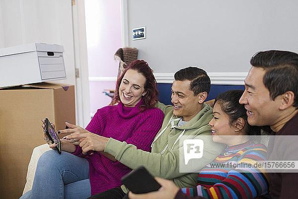 Friends taking a break from moving  using digital tablet