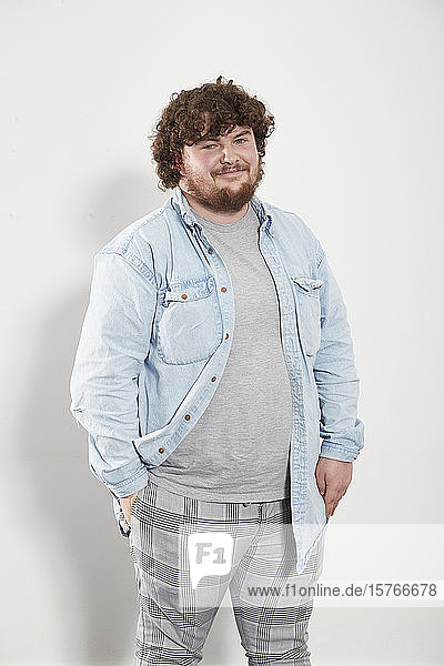 Portrait smiling young man in denim shirt and plaid pants