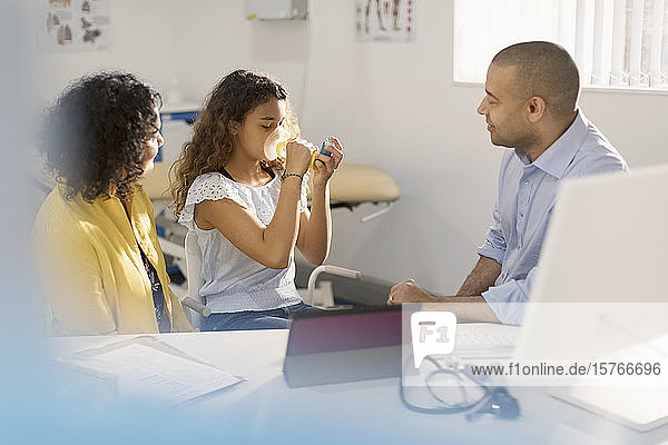 Male pediatrician teaching girl patient how to use inhaler in doctors office