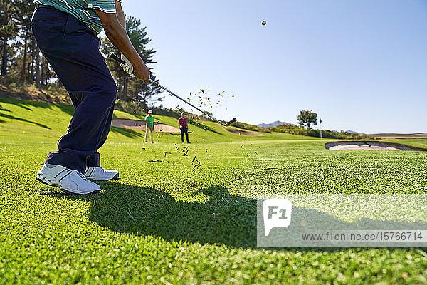 Männlicher Golfer bei einem Schlag auf dem sonnigen Golfplatz