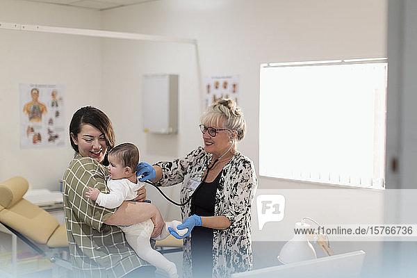Eine Kinderärztin untersucht ein kleines Mädchen im Untersuchungsraum