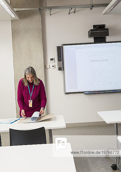 Mature female instructor preparing in classroom