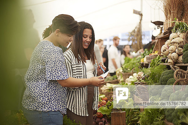 Lesbian couple checking list  shopping at farmer's market