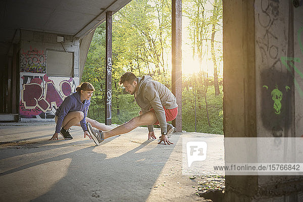 Runners stretching legs in abandoned building