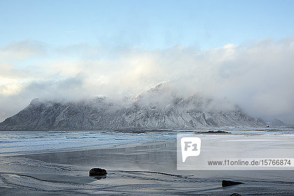 Clouds over snow covered mountain ocean Skagsanden Lofoten Norway