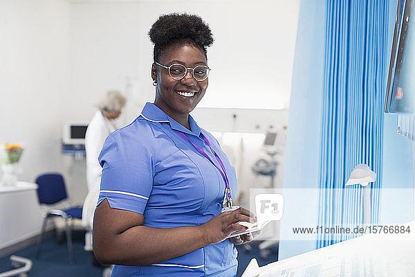 Portrait confident female nurse using digital tablet in hospital room Portrait confident female nurse using digital tablet in hospital room
