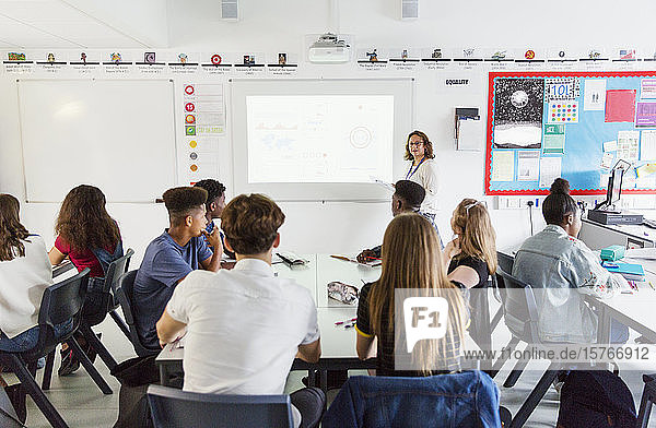 High school students watching female teacher leading lesson at projection screen in classroom