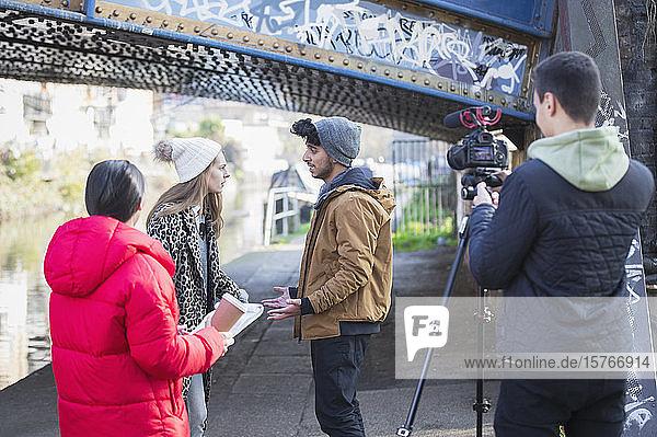 Junge Erwachsene beim Vlogging unter einer Stadtbrücke