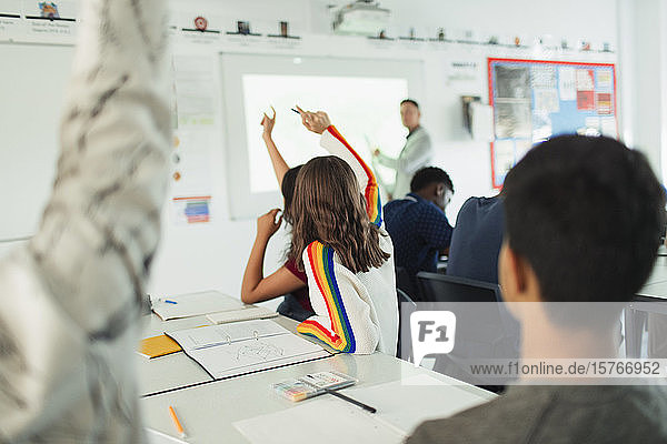 High school students with hands raised during lesson in classroom