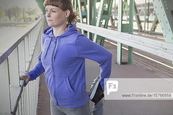 Young female runner stretching leg along urban railing
