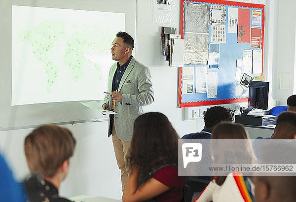 Gymnasiallehrer,  der eine Geografiestunde an der Projektionsfläche im Klassenzimmer leitet