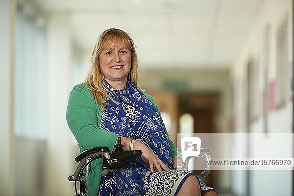 Portrait confident woman in wheelchair in corridor