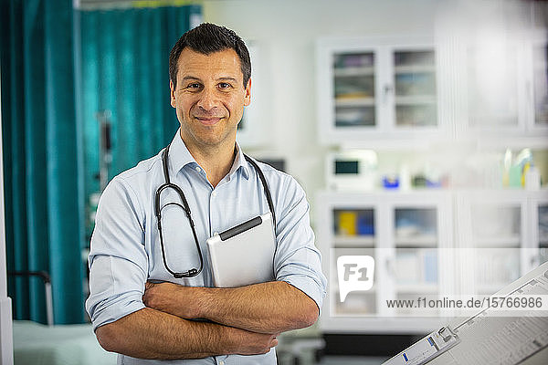 Portrait confident male doctor with digital tablet in hospital room