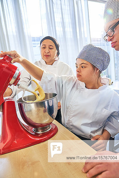 Students with Down Syndrome using stand mixer in baking class Students with Down Syndrome using stand mixer in baking class