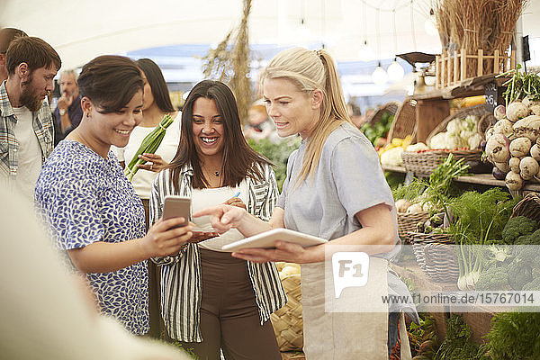 Women with digital tablet and smart phone working at farmer's market