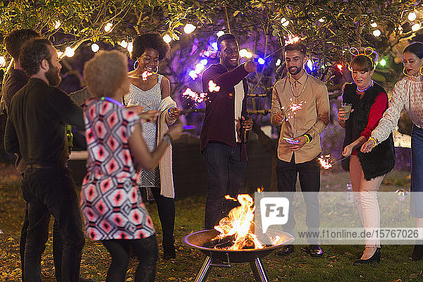 Friends with sparklers around fire pit at garden party