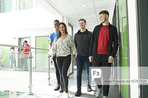 College students walking in sunny corridor