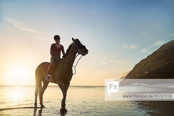 Portrait young woman horseback riding on tranquil sunset ocean beach