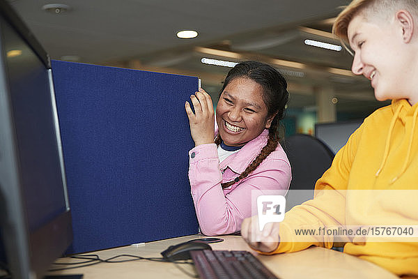 Happy young female college students laughing at computer in library