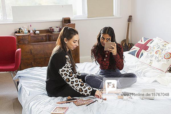Teenager-Mädchen schminken sich  hängen auf dem Bett herum
