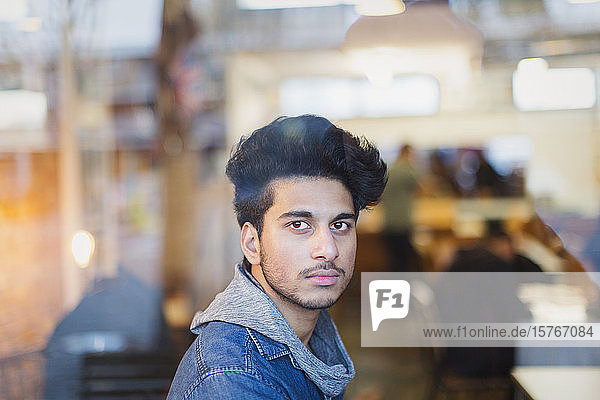 Portrait confident young man in cafe window