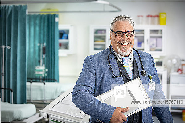 Portrait confident senior male doctor making rounds in hospital Portrait confident senior male doctor making rounds in hospital