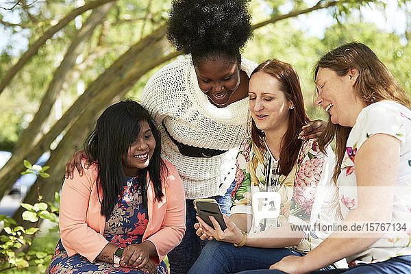 Female friends using smart phone in park